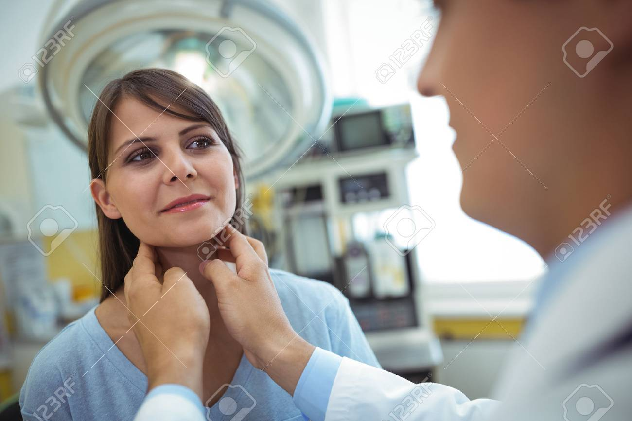 Doctor examining a female patients neck in the hospital - 69179684