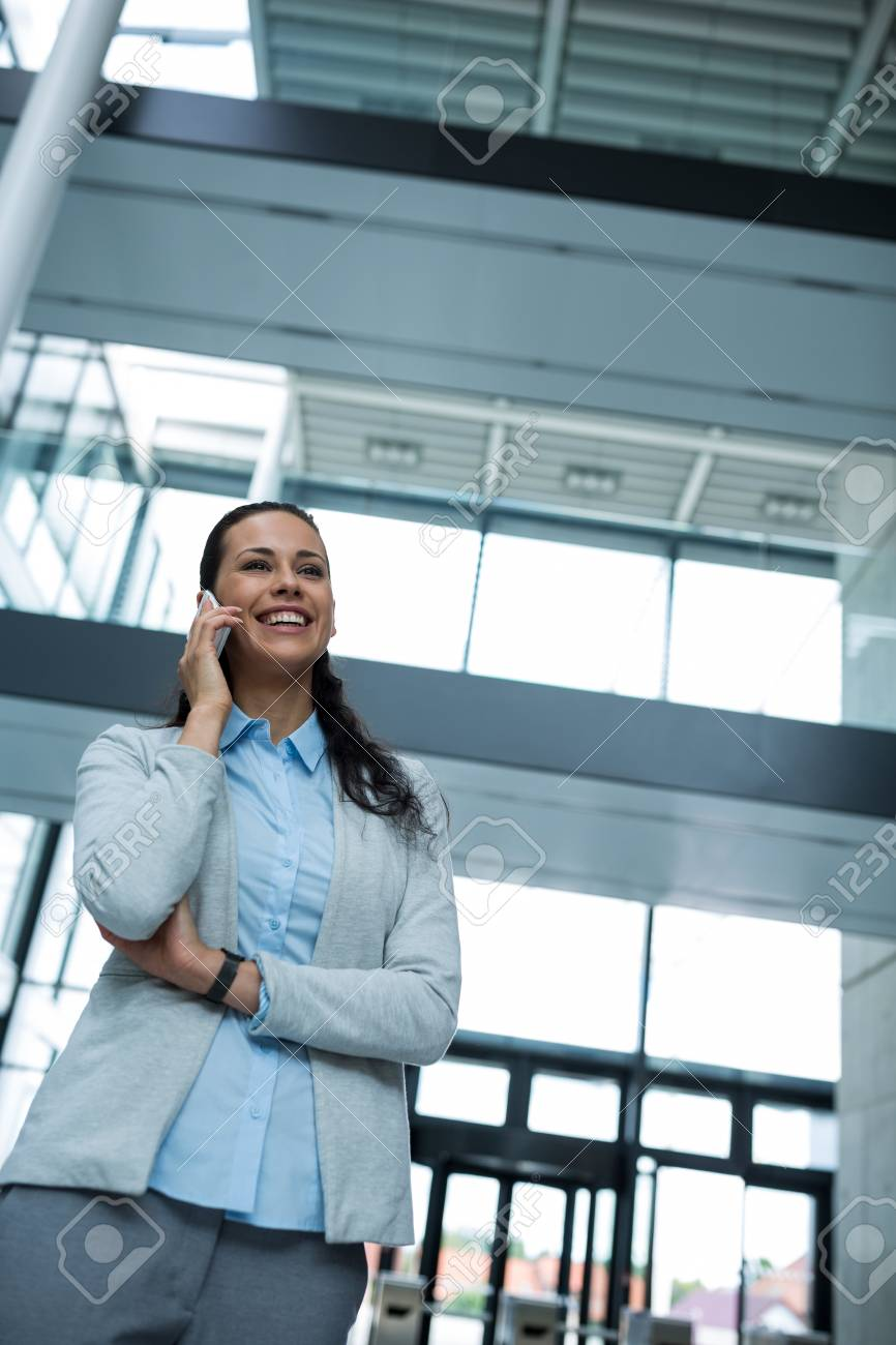 Happy Businesswoman Talking On Mobile Phone In Office