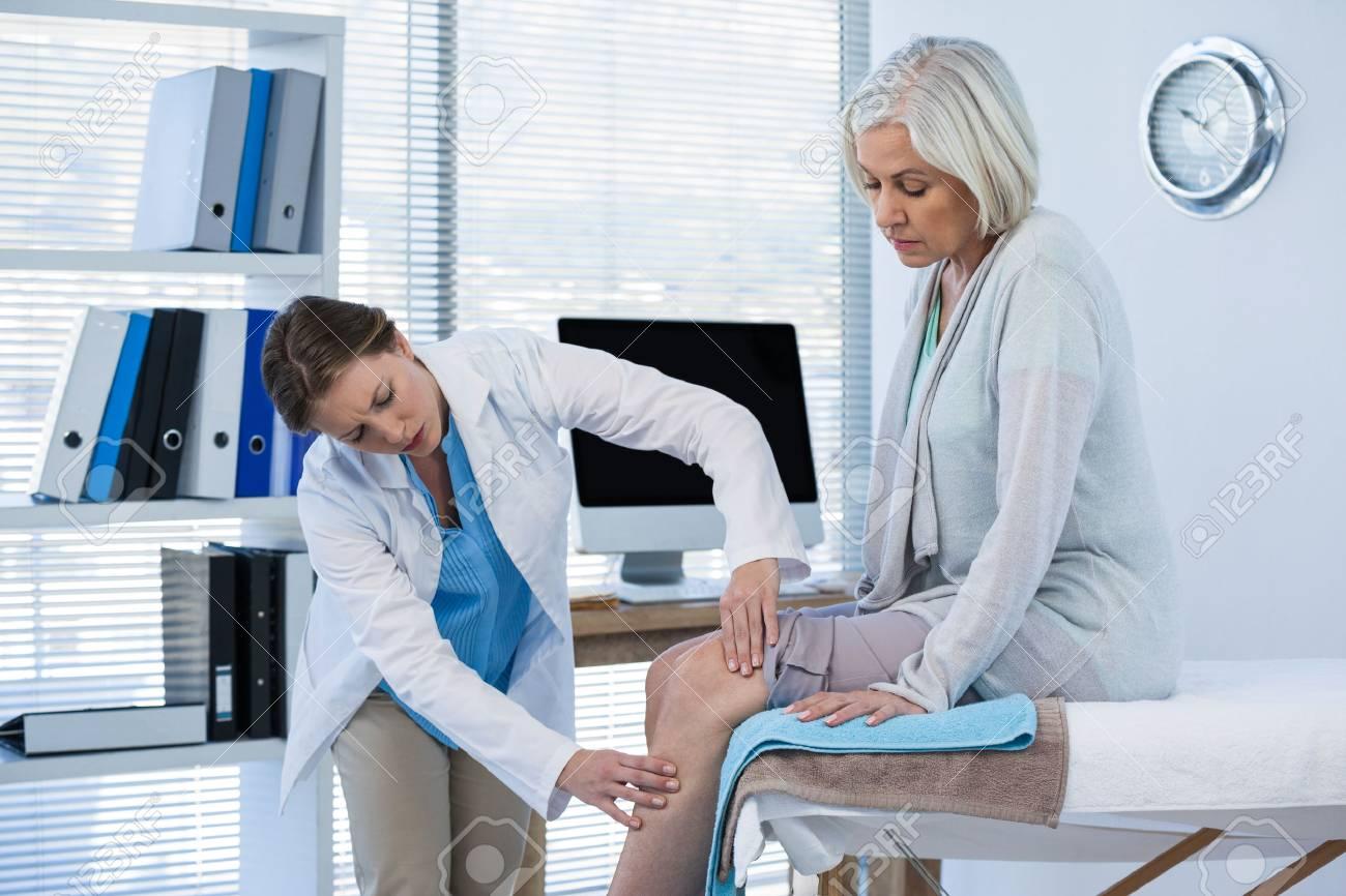 Doctor examining patient knee in clinic - 69596236