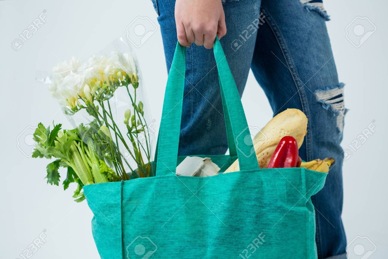 Mid section of woman carrying grocery bag against white background - 69339449