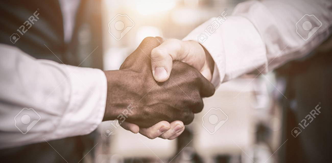 Cropped image of businessman shaking hand with colleague in office - 69609261