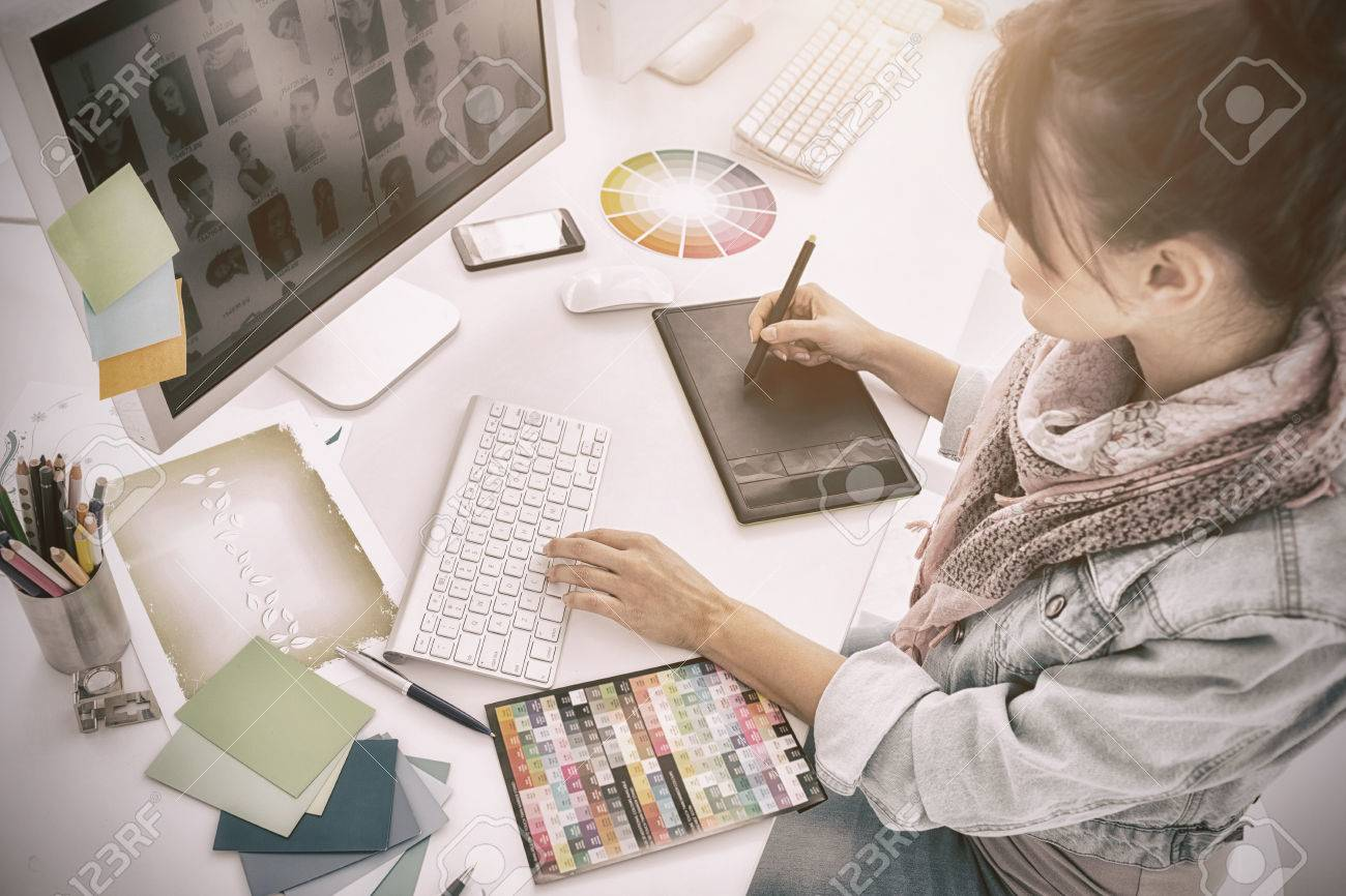 High angle view of an artist drawing something on graphic tablet at the office - 69609716