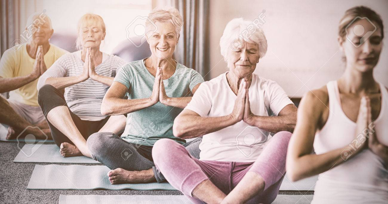 Instructor performing yoga with seniors during sports class - 70189886