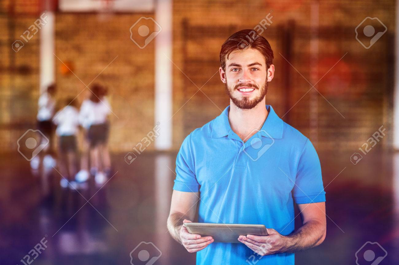 Portrait of sports teacher using digital tablet in basketball court at school gym - 70084225
