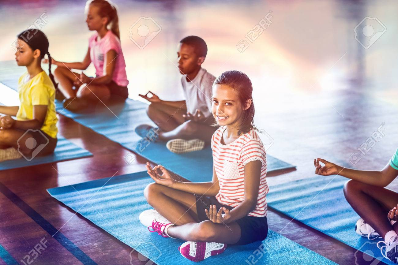 School kids meditating during yoga class in basketball court at school gym - 70084295