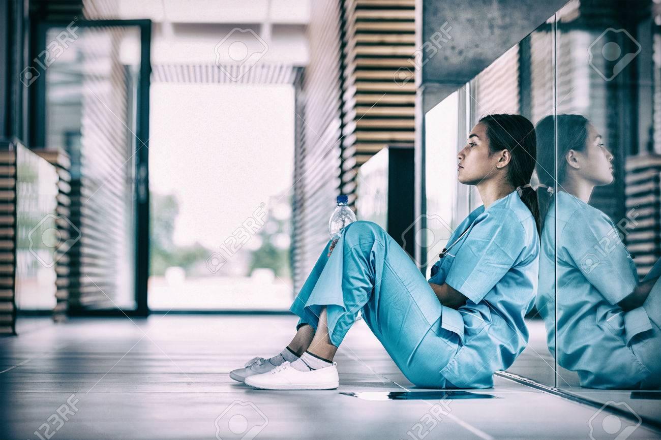 Side view of nurse sitting on floor in hospital corridor - 71083333