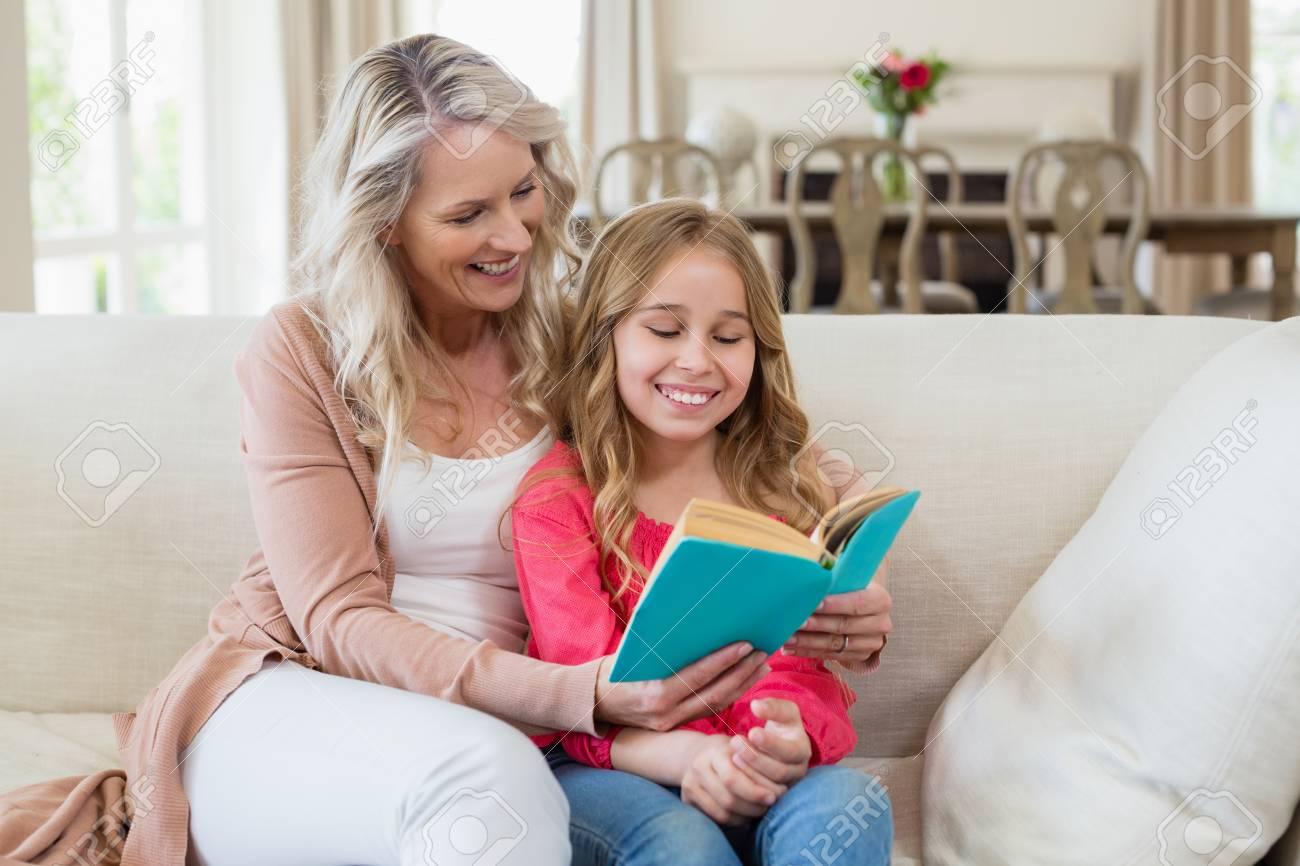 Madre E Hija Leyendo Una Novela En El Sofá En La Sala De Estar En