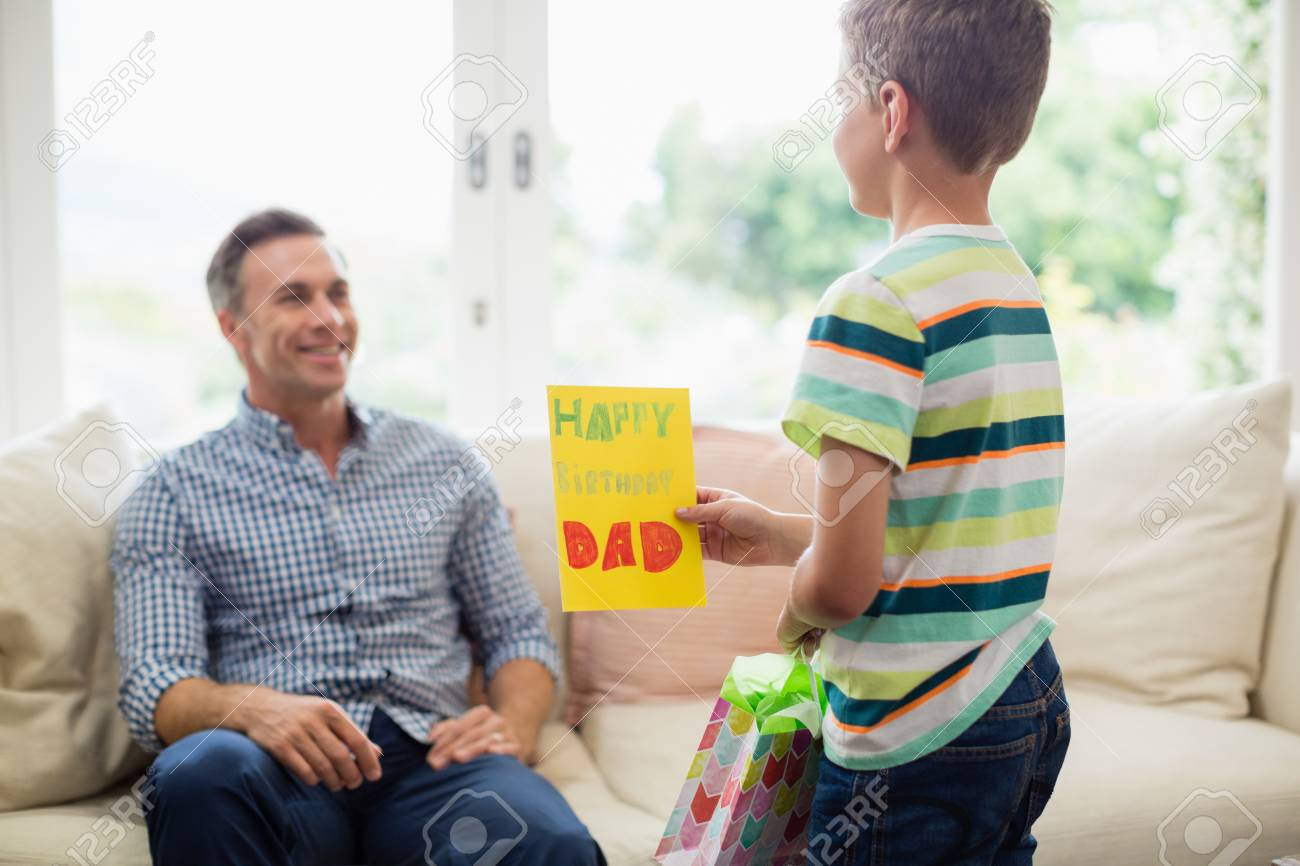 Son Giving Birthday Card To Father In Living Room At Home Stock Photo