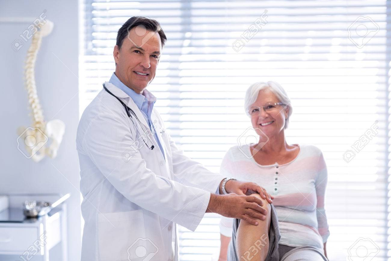 Portrait of physiotherapist giving knee therapy to senior woman in clinic - 71206155