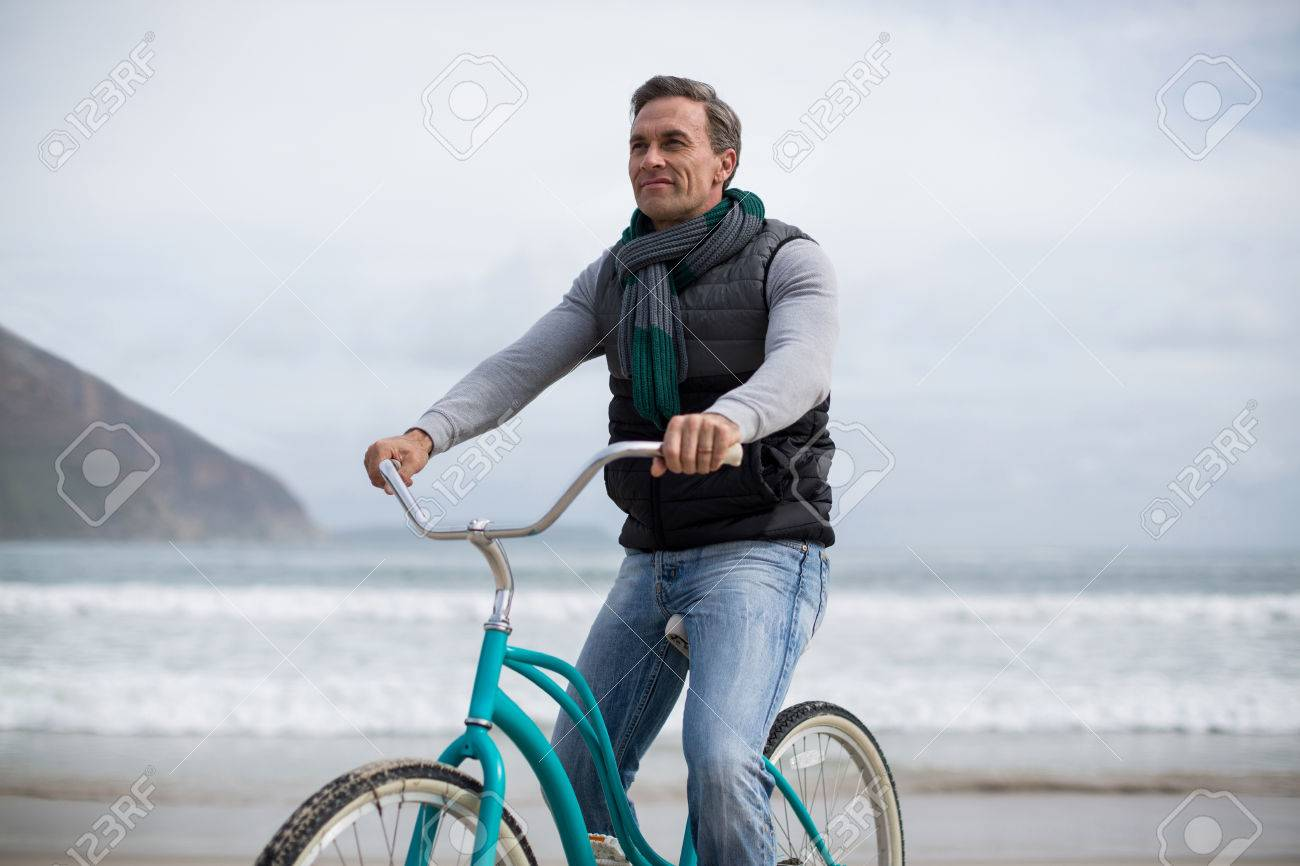 smiling mature man riding bicycle on the beach stock photo, picture