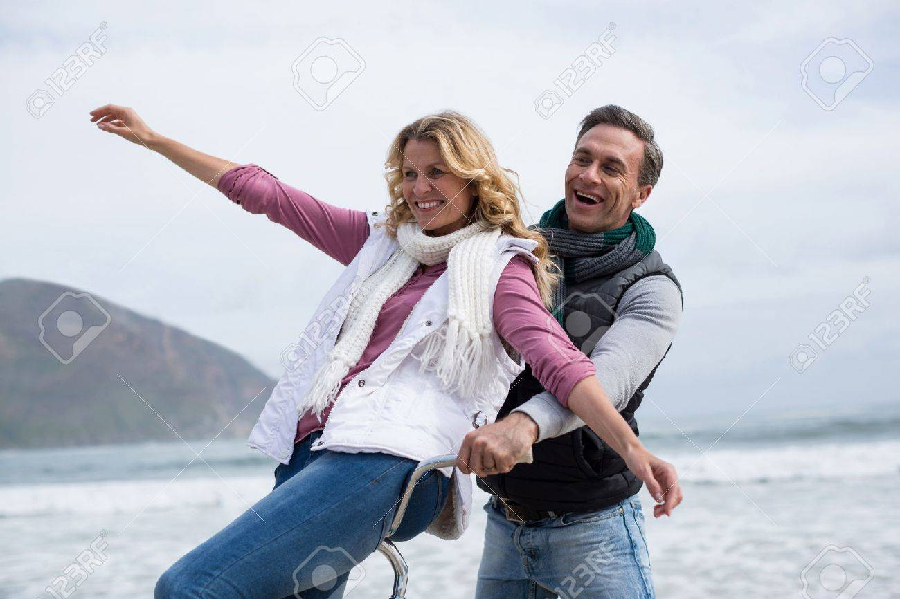 Happy mature couple riding bicycle on the beach - 71360488