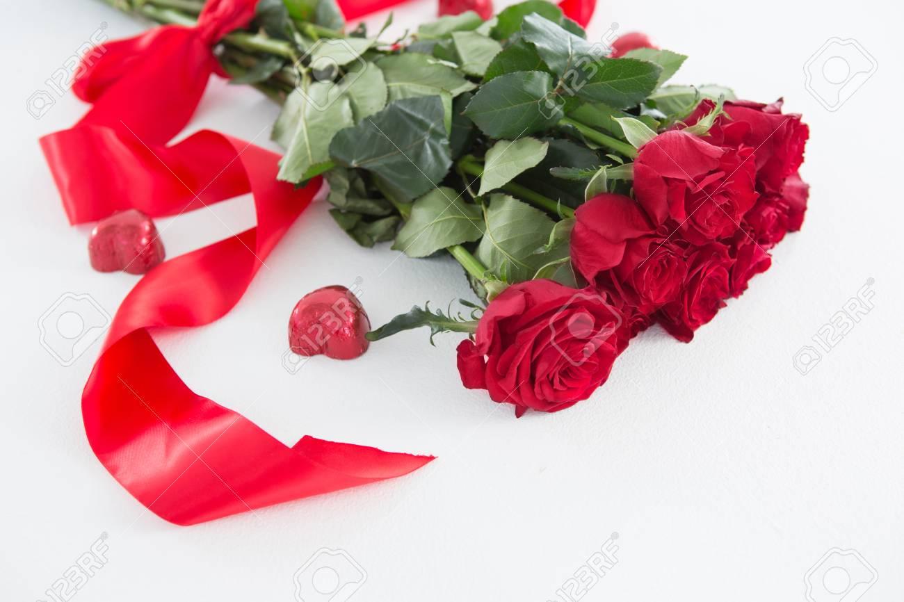 bouquet de roses rouges entouré de chocolat en forme de coeur sur