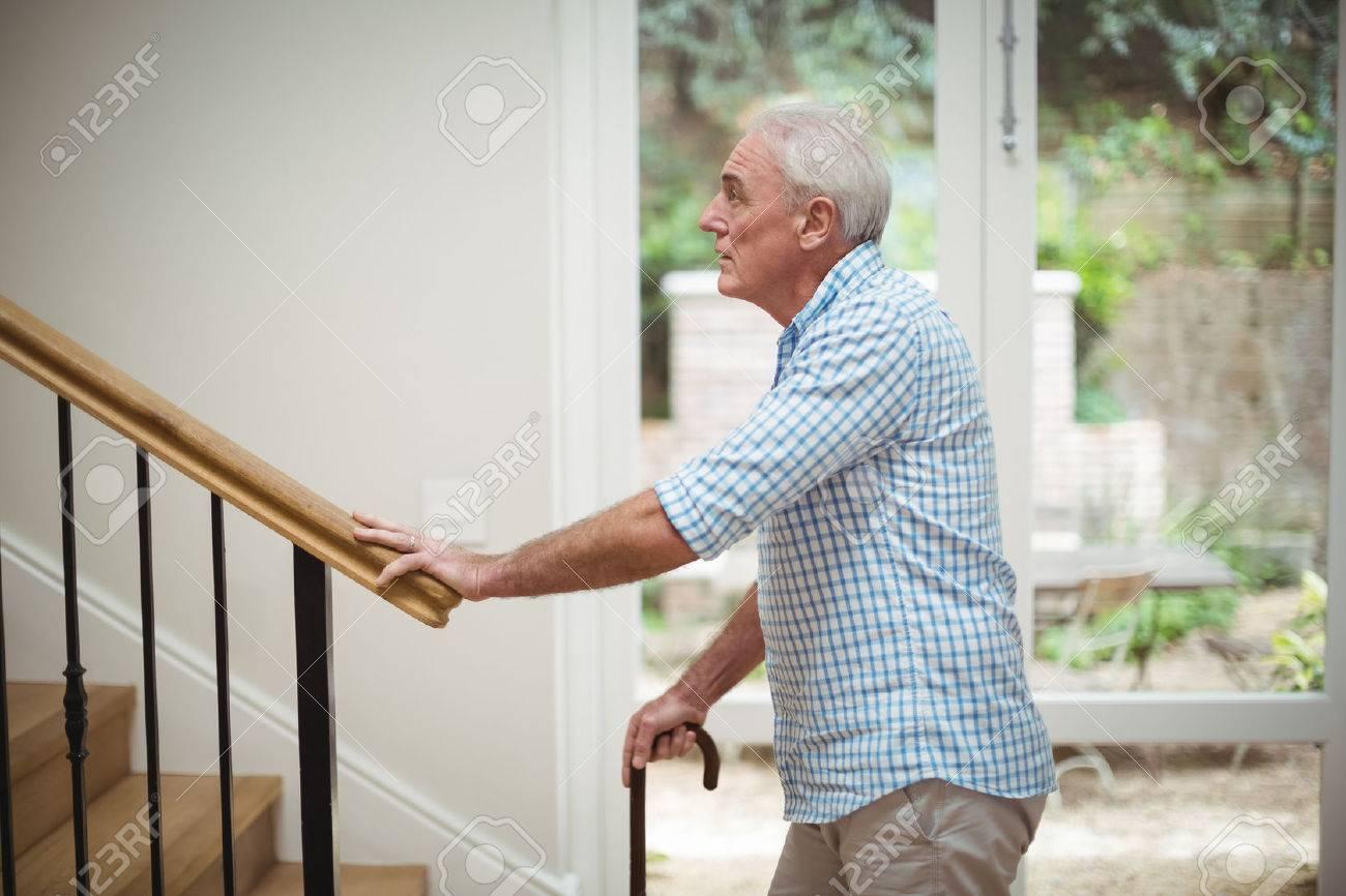 Senior man climbing upstairs with walking stick at home Stock Photo - 71971138