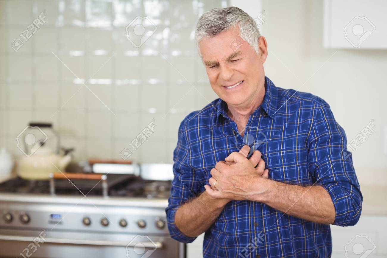Senior man suffering from heart attack in kitchen at home - 72010511