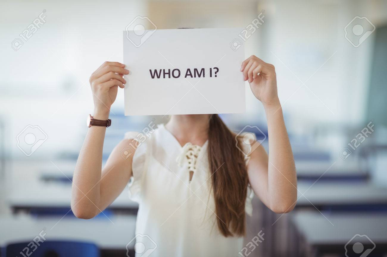 Schoolgirl holding white paper with text sign in classroom at school - 72663138