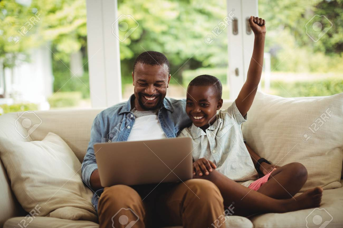 Father and son using laptop in living room at home - 72662840