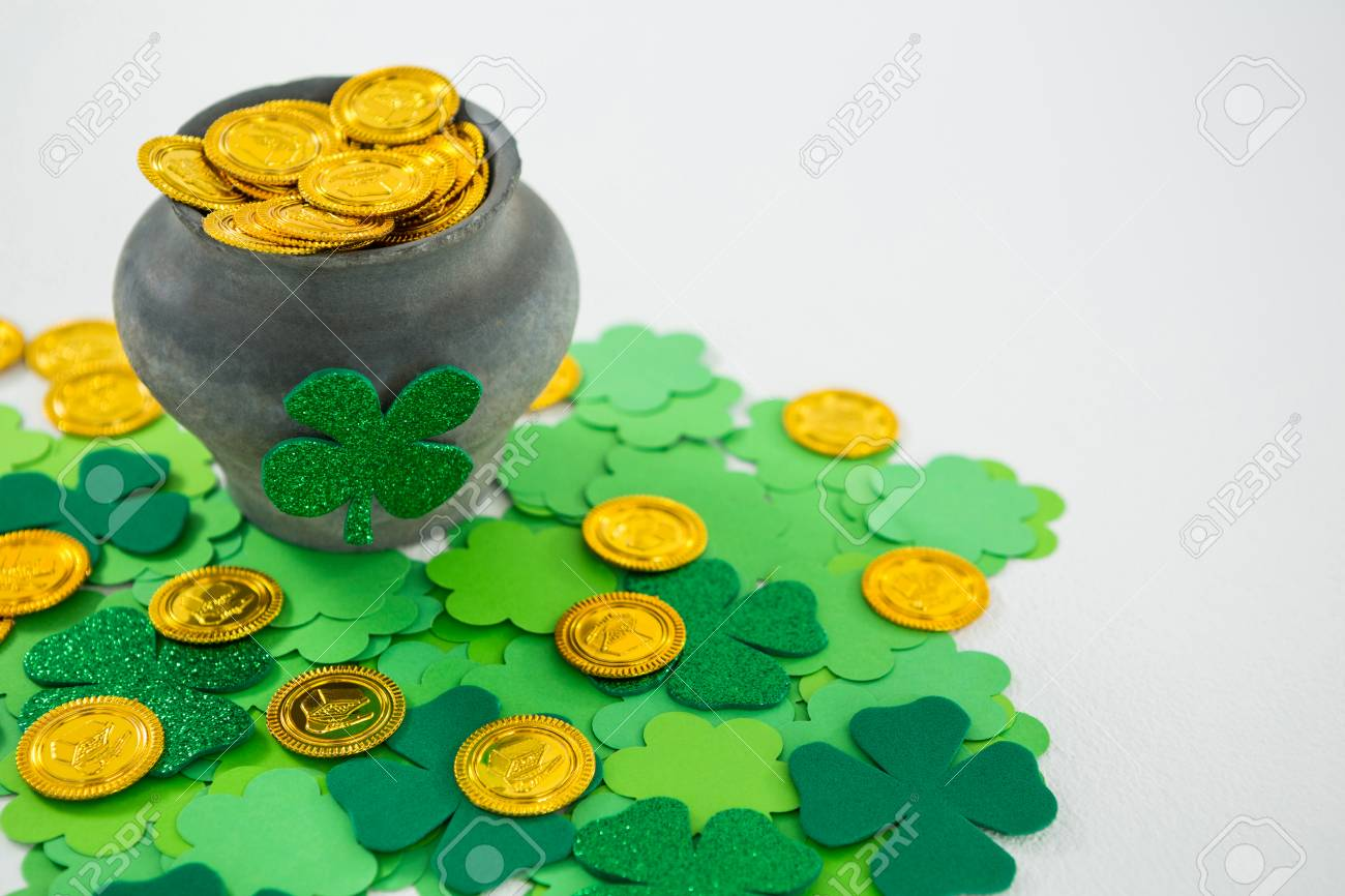 St Patricks Day Shamrock And Pot Filled With Chocolate Gold Coins On White Background Stock