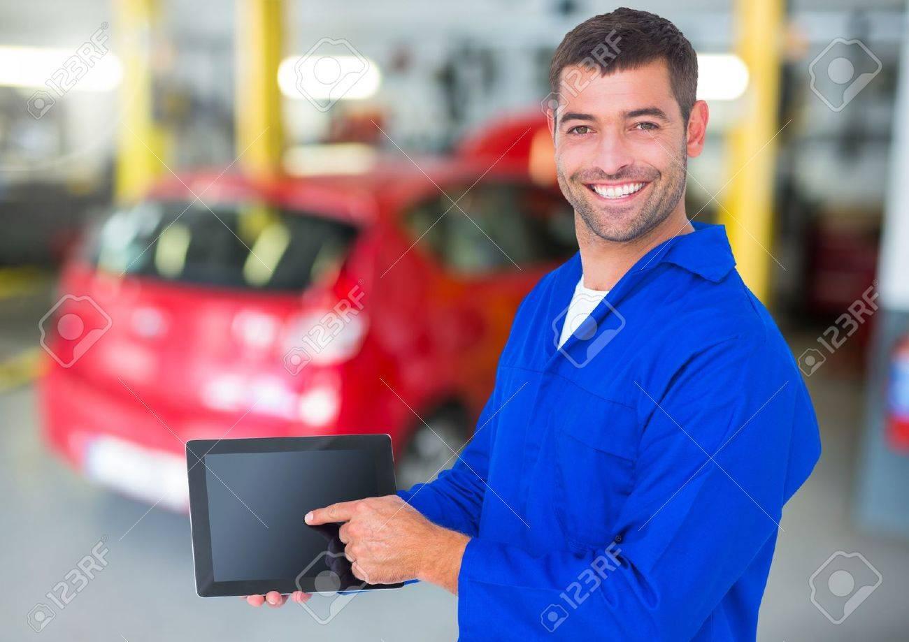 Portrait of a happy automobile mechanic holding a digital tablet - 72791933