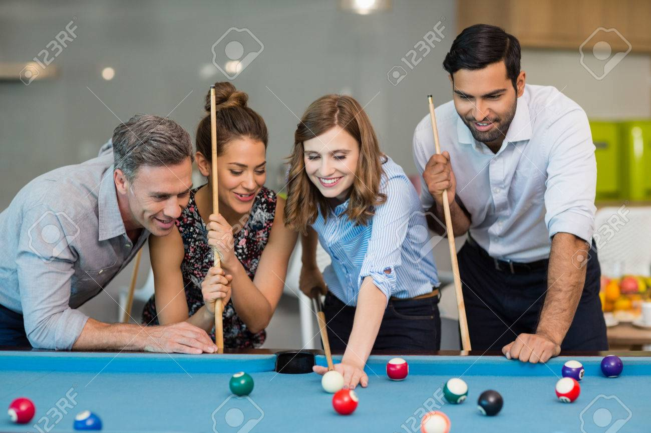 Smiling business colleagues playing pool in office space - 72895876