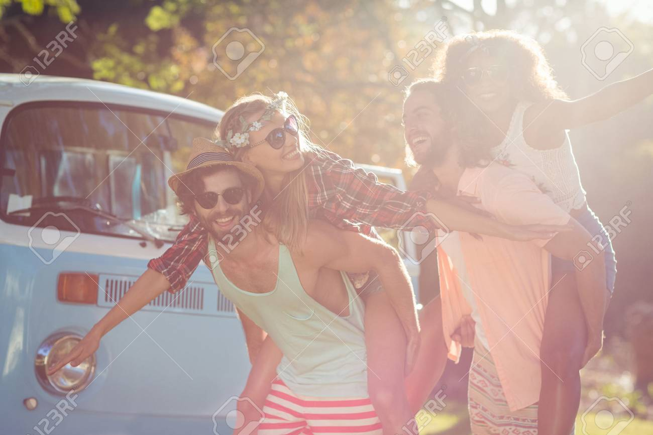Two happy couples having piggy ride in park on a sunny day Stock Photo - 73436153