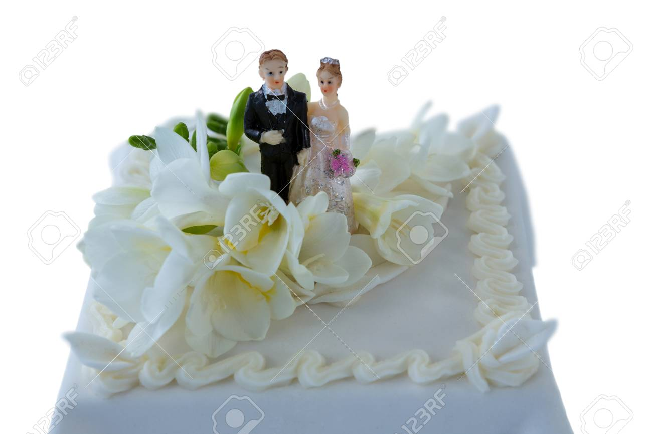 Wedding Cake With Couple Figurines And Flowers Against White Stock