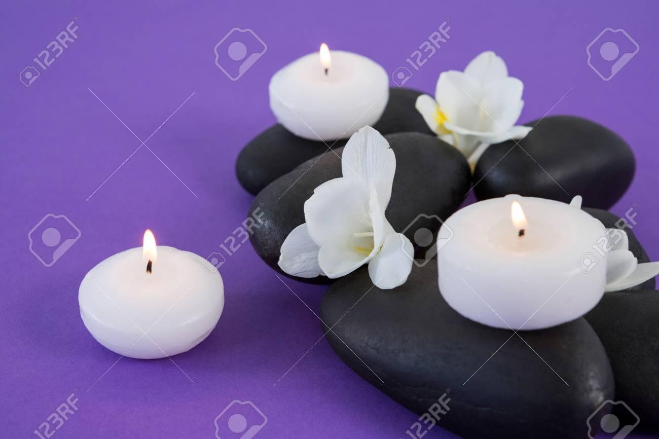 White Flowers Candles On Zen Stone On Purple Background Stock Photo