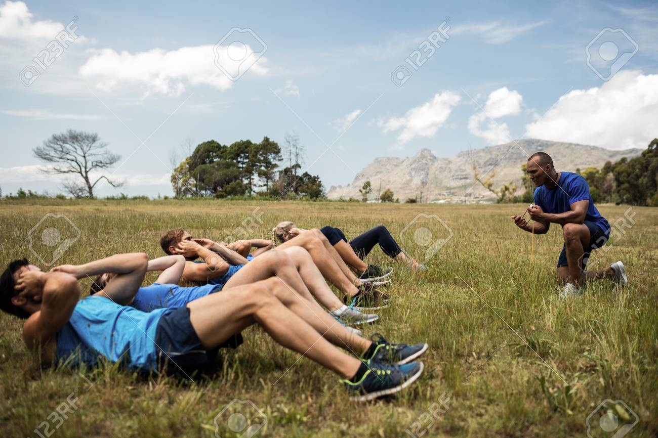 Fit people performing crunches exercise in bootcamp - 74454699