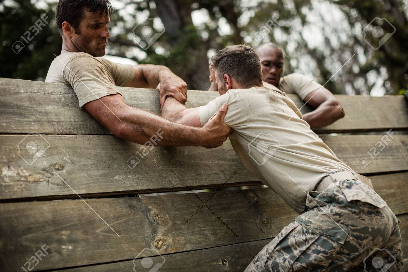 Soldiers helping man to climb wooden wall in boot camp - 74454726