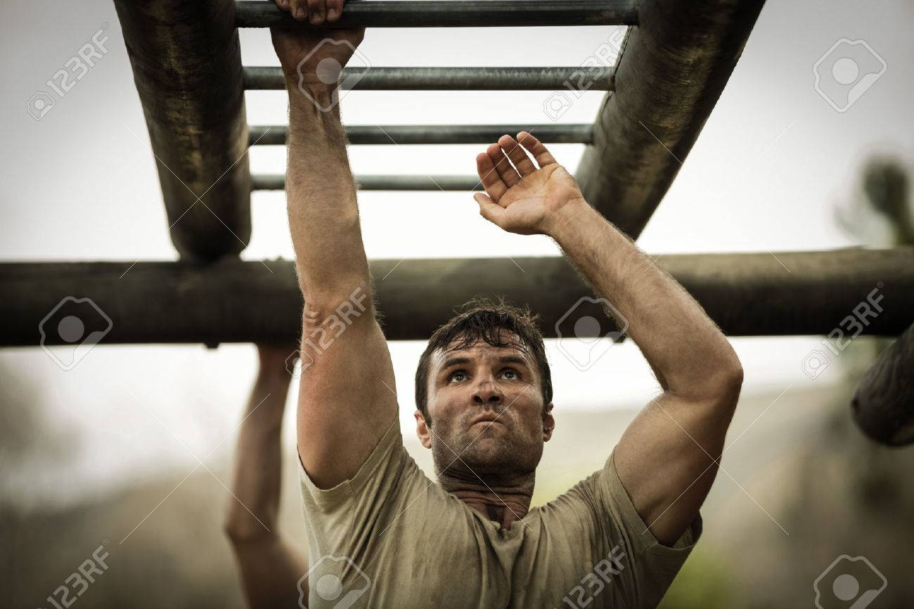 Soldier climbing monkey bars in boot camp - 74454882
