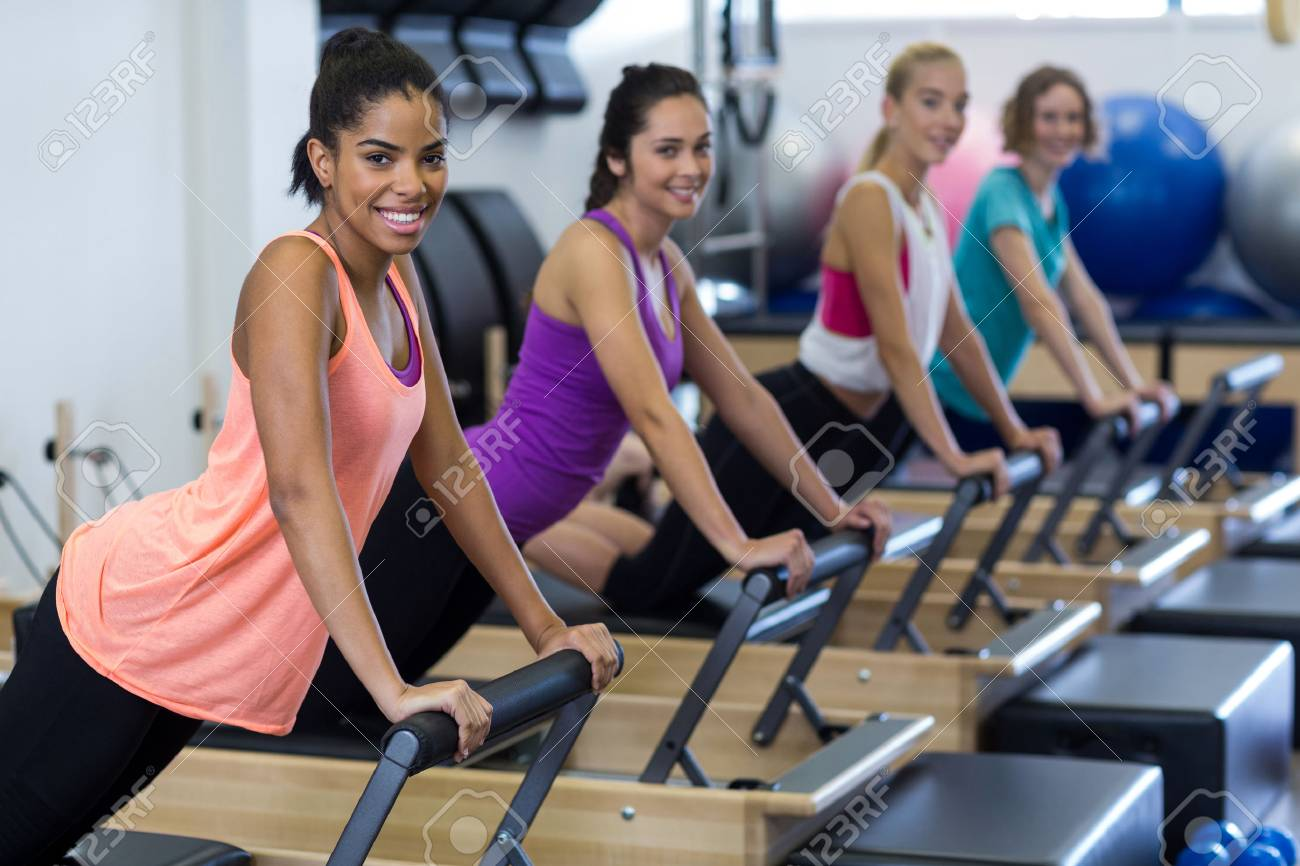 Group of women exercising on reformer in gym - 75139863