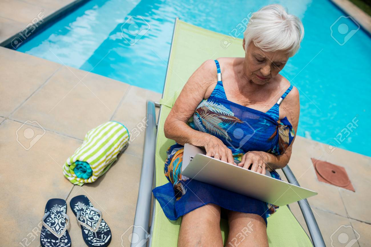 74694748-senior-woman-using-laptop-on-lounge-chair-at-poolside.jpg