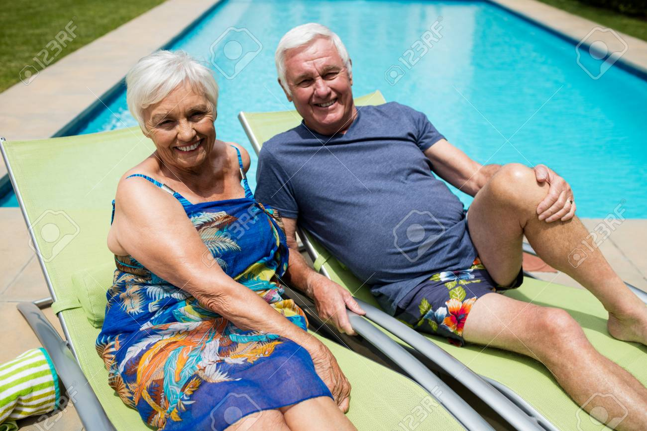 Charmant Portrait Of Senior Couple Relaxing On Lounge Chair At Poolside Stock Photo    74695030