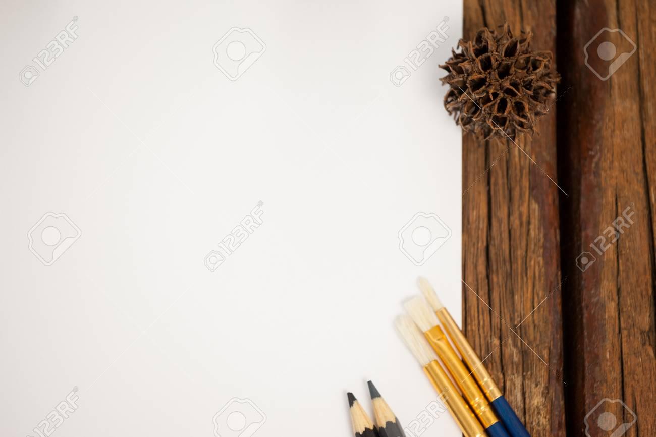 Tavolo Da Disegno Artistico : Pigna tenuta sul bordo della carta da disegno bianca sul tavolo di