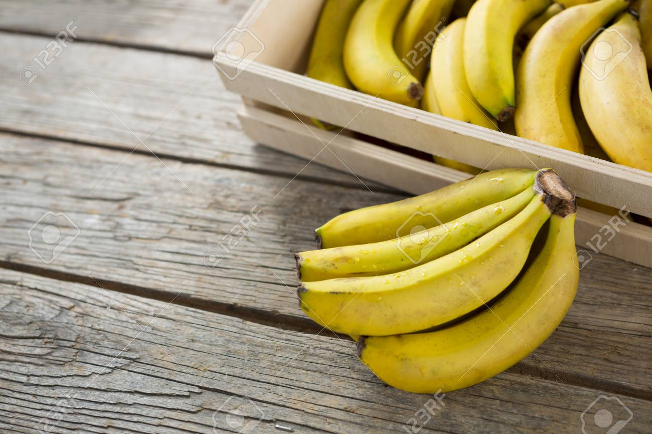 Banana On Table Bananas in wooden crate on wooden table Stock Photo - 74960439