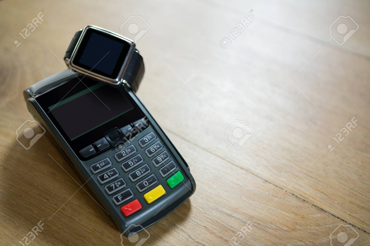 8b86fb1de90 Close-up of smart watch and credit card reader on table in coffee shop Stock