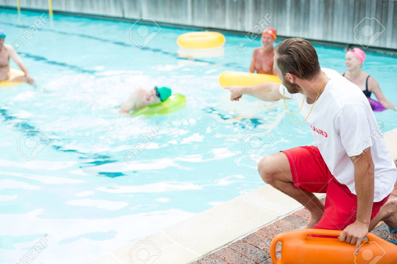 Male lifeguard assisting swimmers at poolside - 75351242