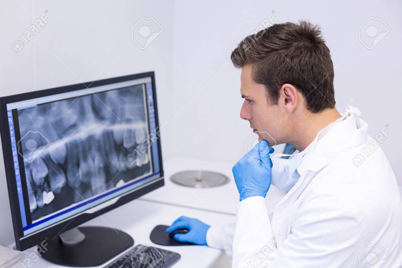 Attentive dentist examining x-ray report on computer in clinic - 75910176
