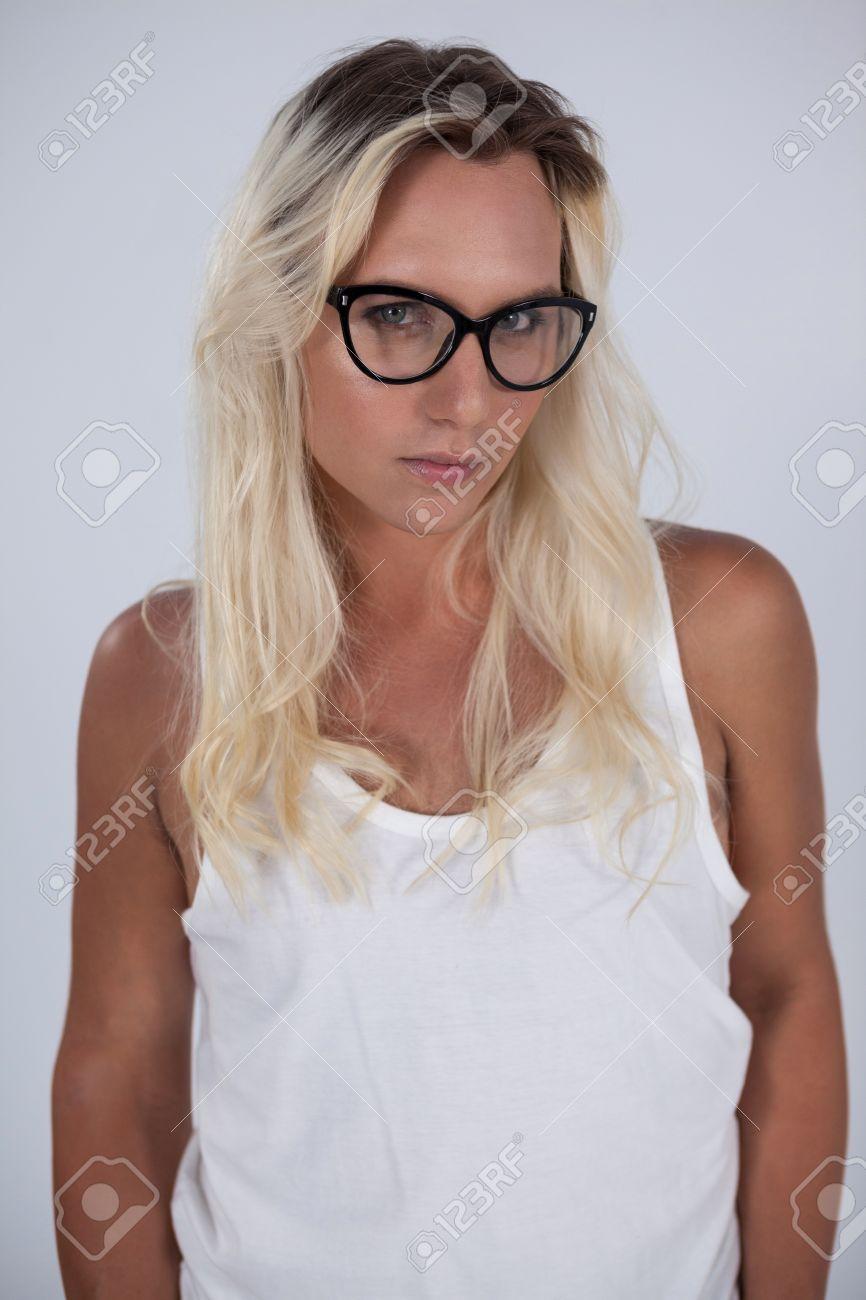400a079a45a008 Mooie transgender vrouw die bril draagt   die over grijze achtergrond staat  Stockfoto - 75908743