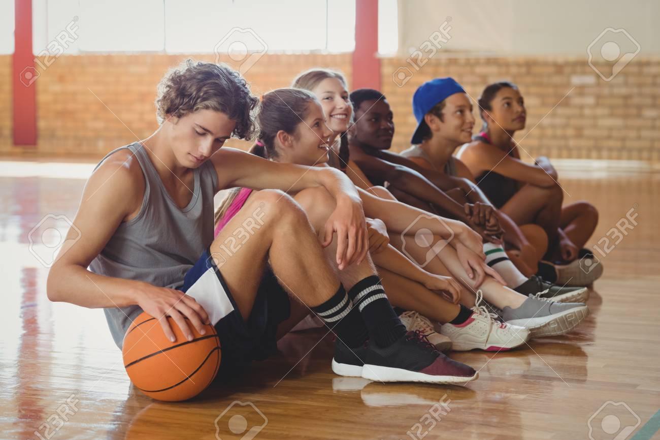 Sol Terrain De Basket lycéens assis sur le sol dans le terrain de basket à l'intérieur