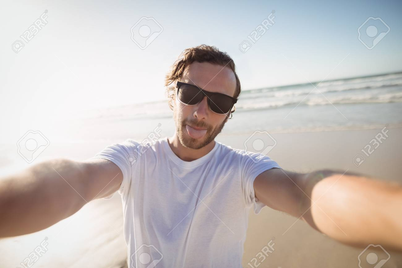 d8117a52877f Portrait of young man wearing sunglasses at beach during sunny day Stock  Photo - 77598945