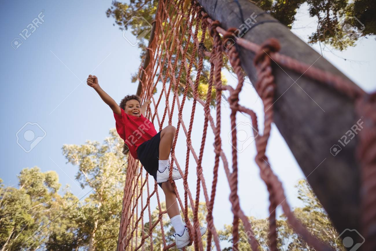 Happy boy cheering while climbing a net during obstacle course in boot camp - 79251725