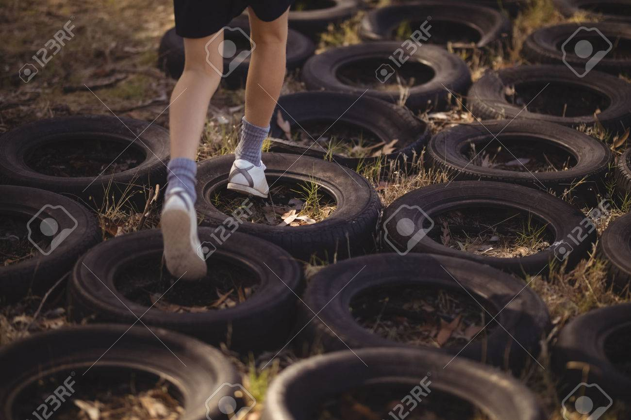 Low section of girl running over tyres during obstacle course - 79252442