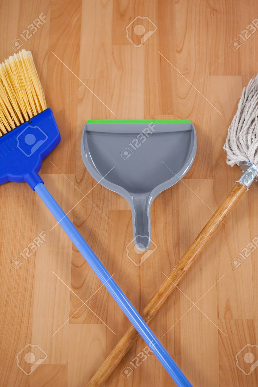 Close-up of dustpan, sweeping broom and mop on wooden floor