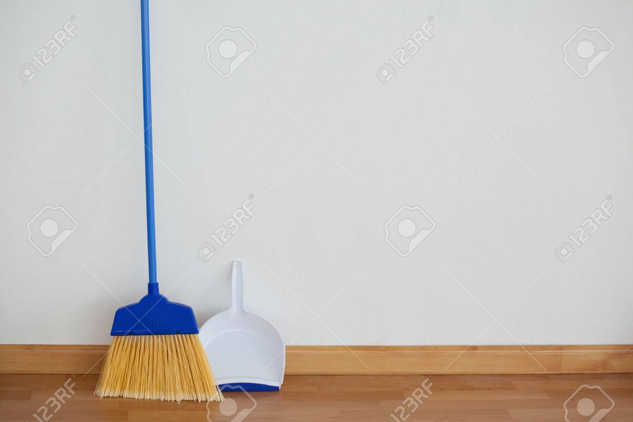 Close-up of dustpan and sweeping broom leaning against white
