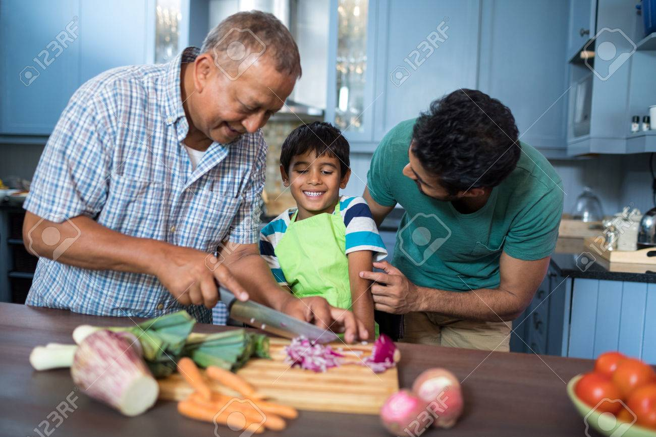 Father Looking At Son While Standing By Man Cutting Onion In.. Stock ...