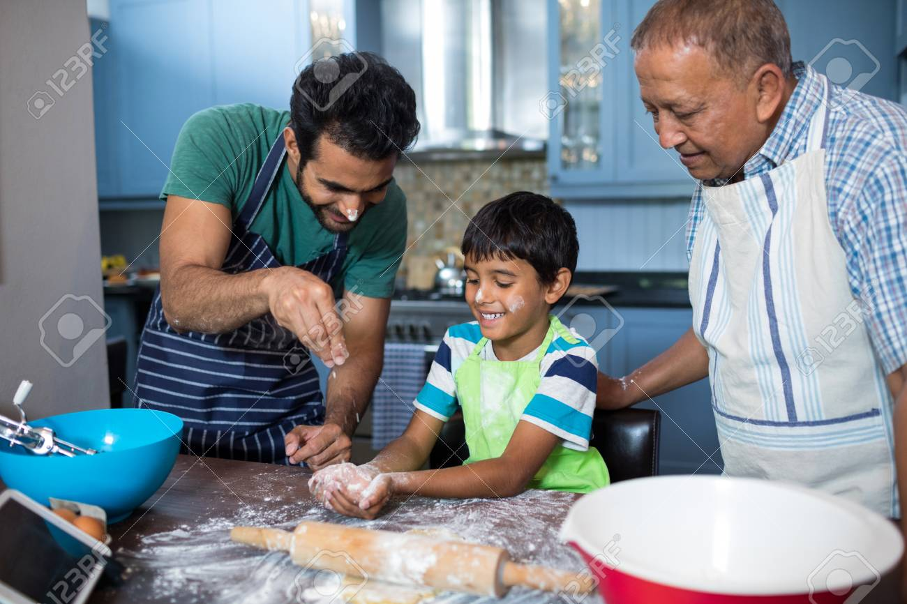 Father Sprinkling Flour On Sons Hand While Preparing Food With ...