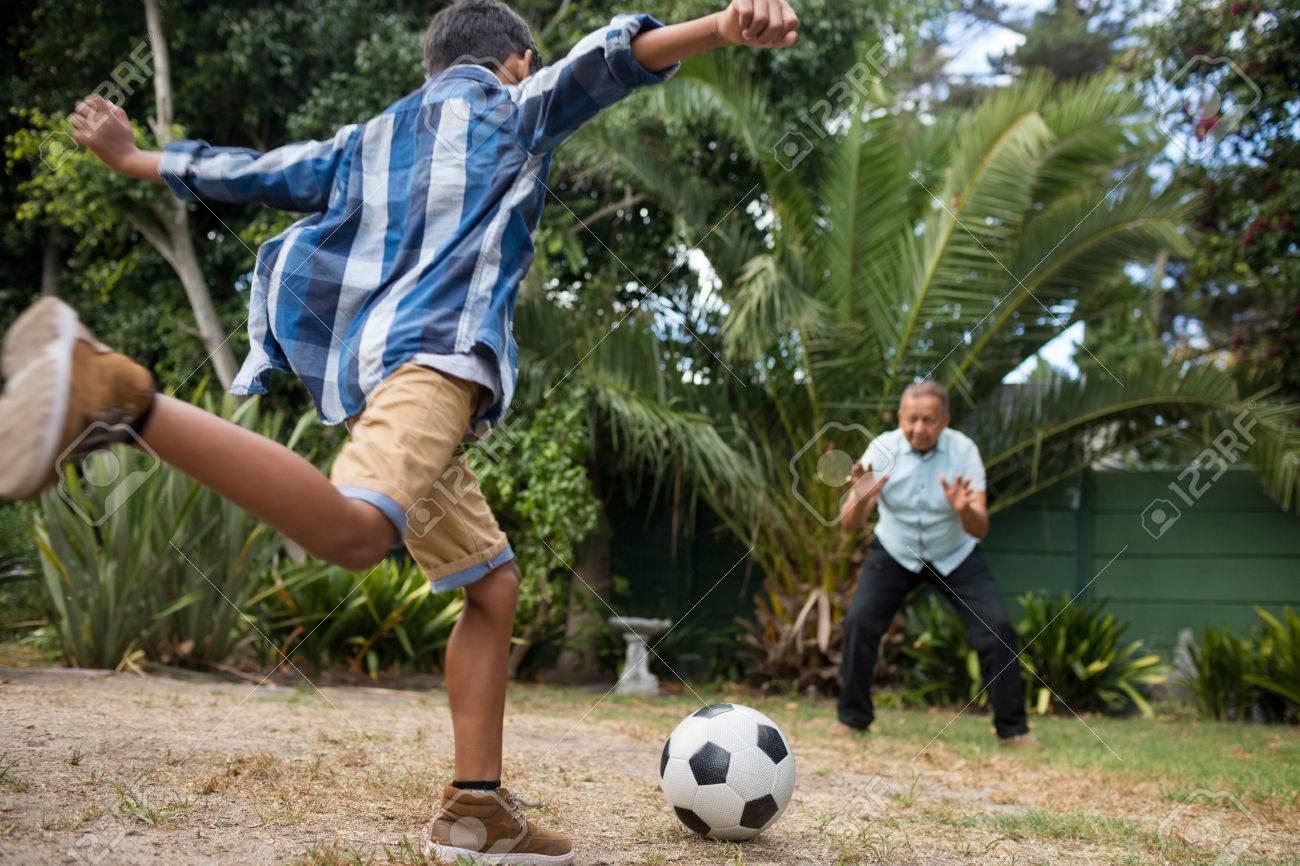 Abuelos Guarros niño jugando al fútbol con el abuelo en el campo en el patio
