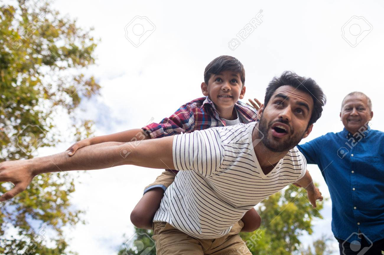 Abuelos Guarros abuelo sonriente que mira al hombre que da el apoyo guarro al hijo con los  brazos saltó en yarda