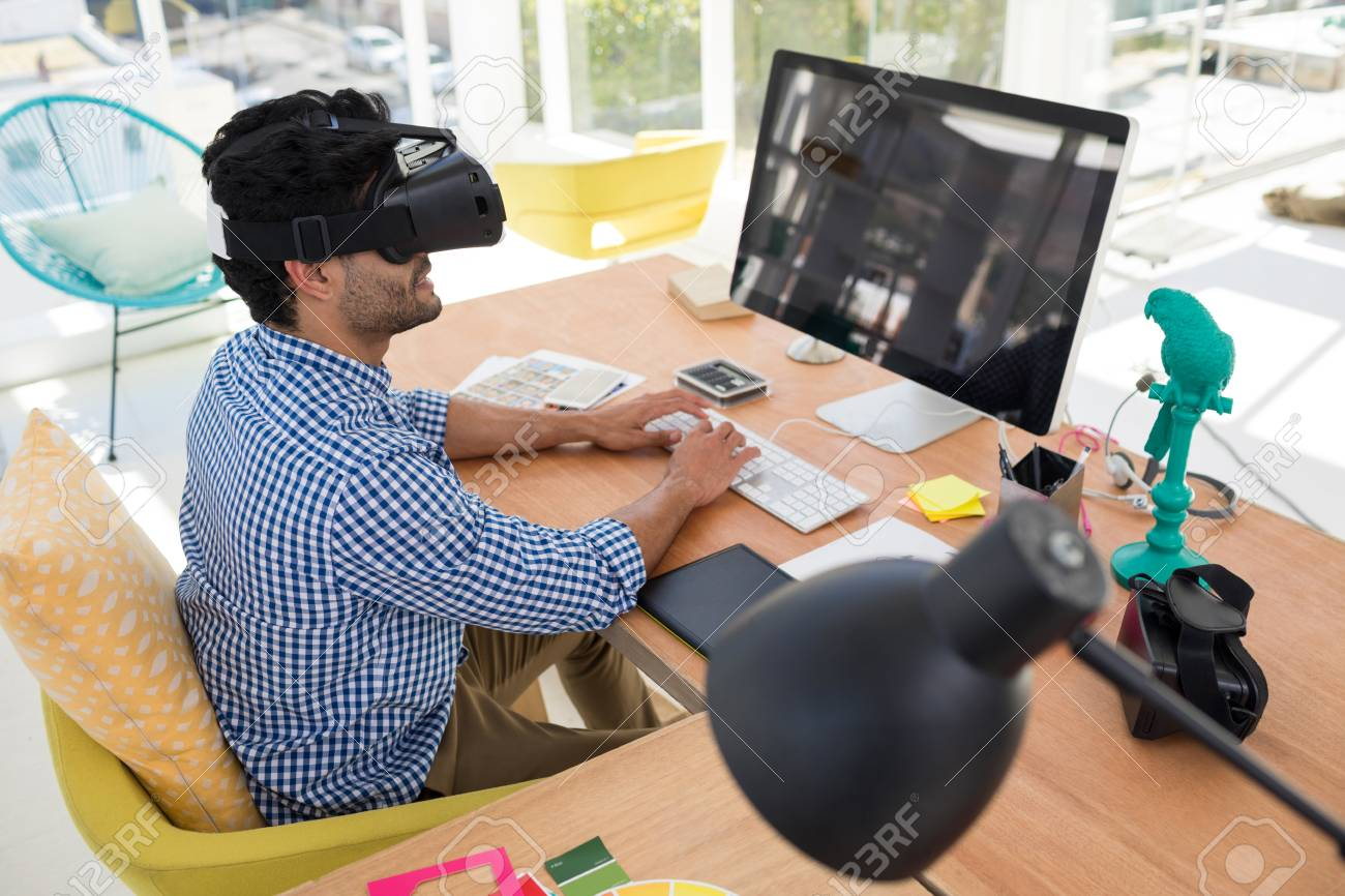 69ca5219bcf Graphic designer in virtual reality headset working on computer at desk in  the office Stock Photo