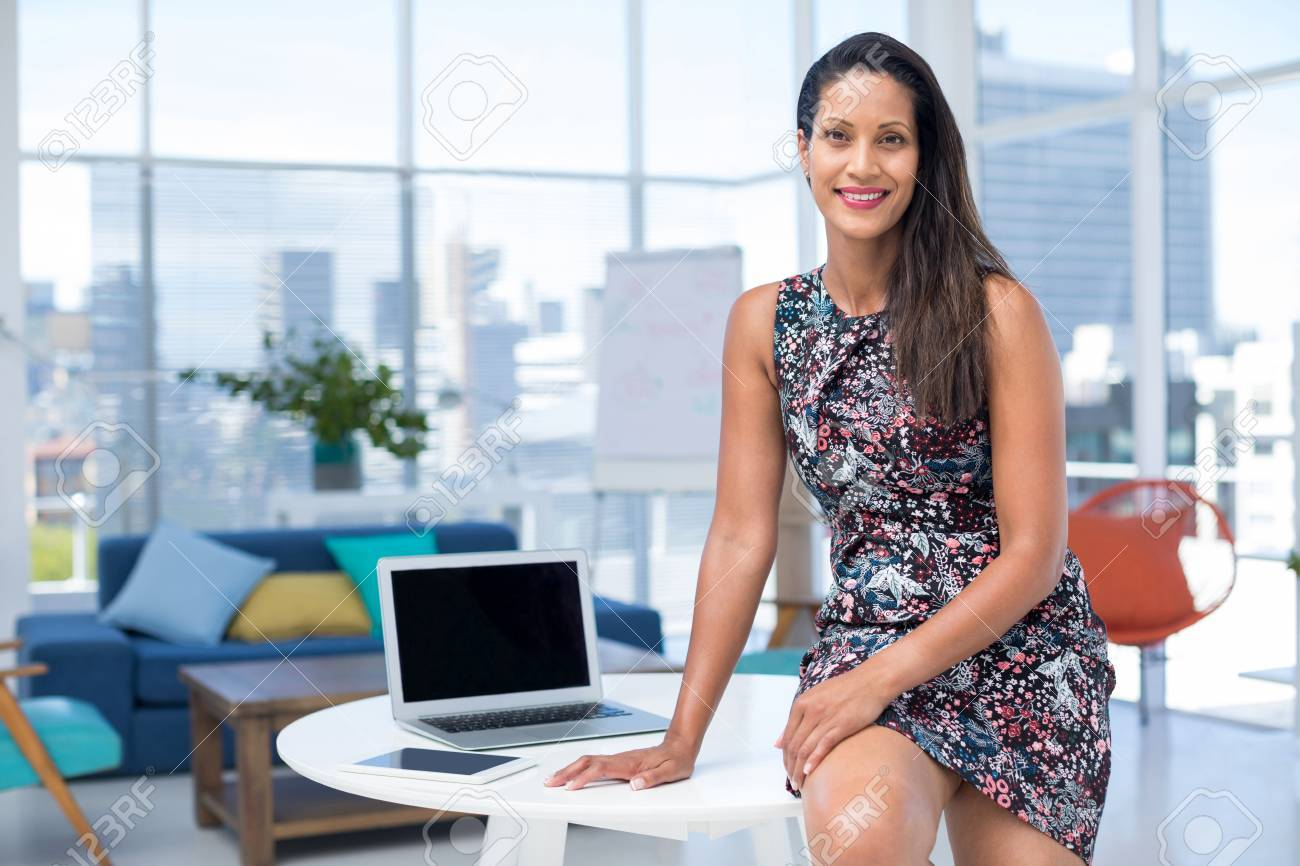 portrait of female executive sitting on desk in the office stock rh 123rf com  female executive office accessories